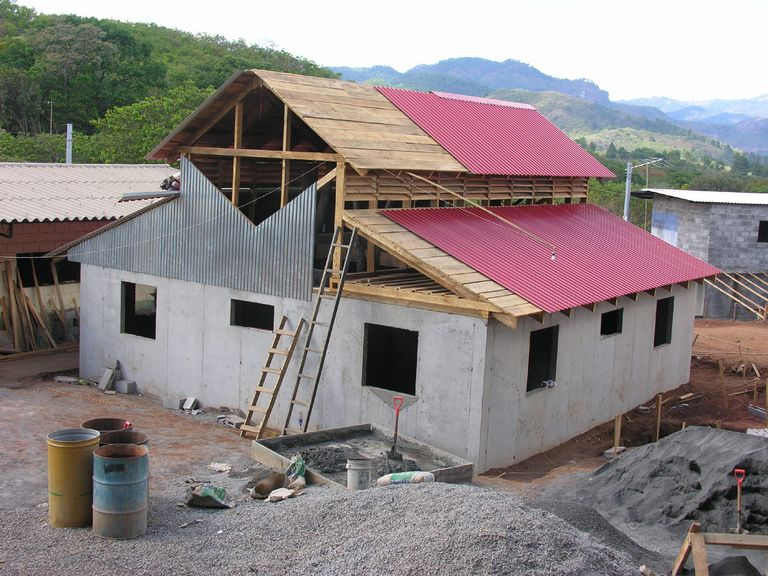 Construction photo of stucco and metal building with metal roof