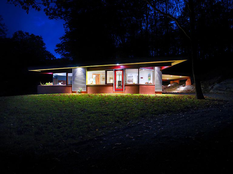 Modern, angular, brightly colored night-time view of small residence