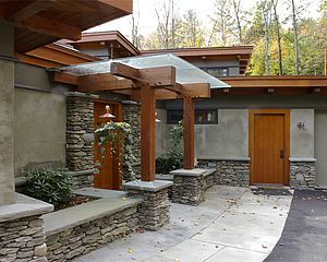 rustic stone and plaster residence with wood doors, trim and columns