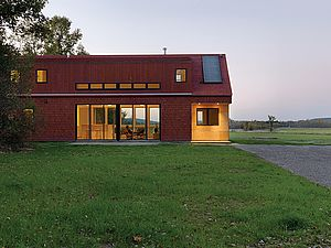 Modern, gable roof exterior with red wood shingle siding and large windows
